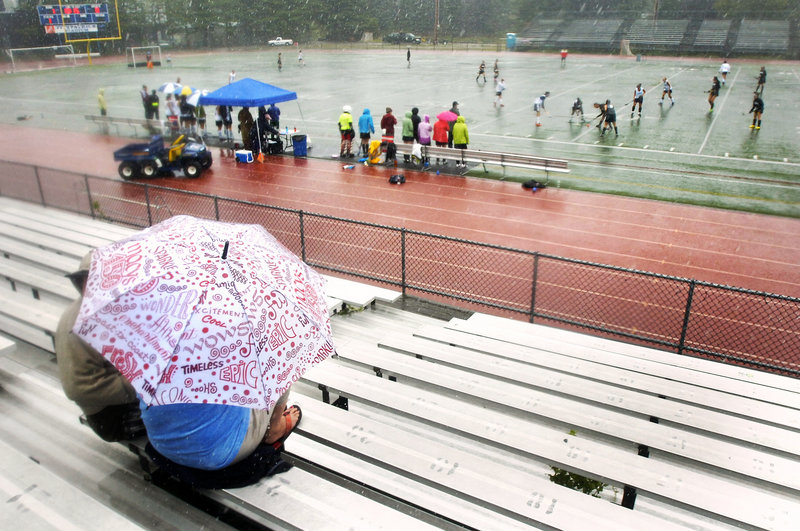 Hey, the kids are playing. And that means neither rain nor … well, rain, and lots of it. But these folks were there for field hockey and support, no matter what.