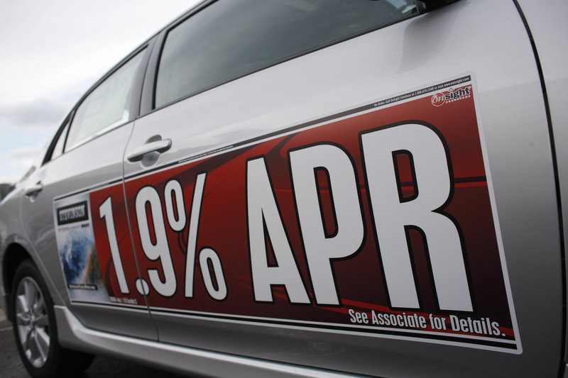 A low-interest rate banner hangs on the side of an 2010 Toyota Corolla at a dealership in Lakewood, Colo. Car owners often pay far more than necessary for financing, but auto loans, like mortgages, can be refinanced.
