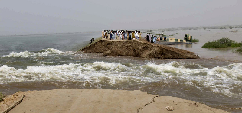 Pakistani villagers stand on the remains of an embankment washed away by heavy flooding near Hyderabad on Thursday. Some 8 million people are in need of emergency aid, but the Taliban doesn't believe foreigners are there to help them.