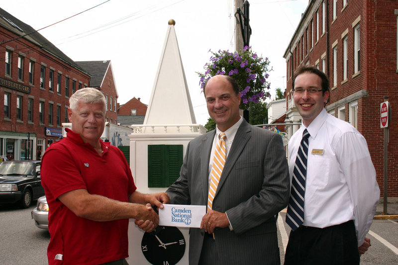 Walter Hilton, left, chairman of the Landmark Steeple & Clock Restoration Fund, receives a check from Greg Dufour, center, and Jim Jarvis, right, both of Camden National Bank.