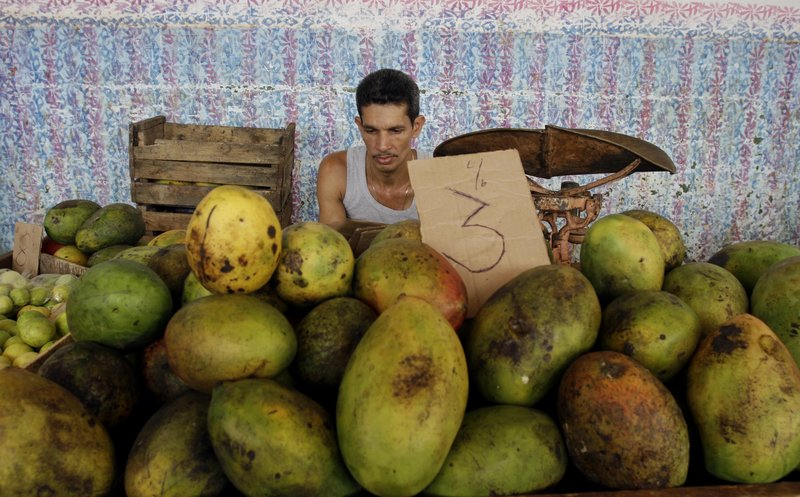 A fruit vendor awaits business at a market in Havana on Friday. He'll be able to sell from home under new commerce rules.