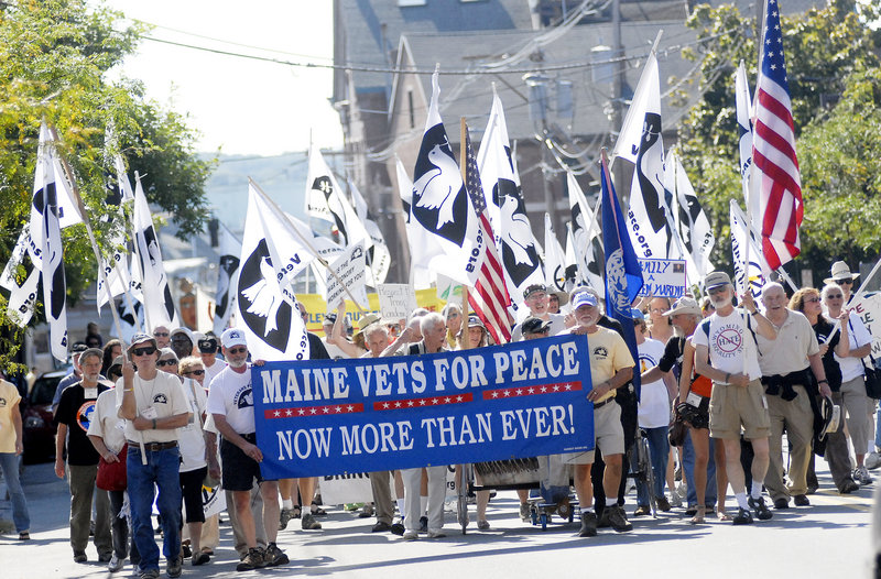 A throng of flag-bearing Veterans for Peace are gathered around their banner as they march through the Old Port Sunday.
