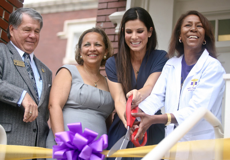 Actress Sandra Bullock, third from left, joins Billy Hatchett, left, Warren Easton Foundation president, Principal Alexina Medley and school nurse Cassondra Ferrand in cutting the ribbon at an on-campus health clinic at Warren Easton Charter High School in New Orleans on Sunday.