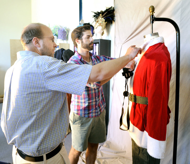 Reporter Ray Routhier, left, adjusts a costume with Jacob Freund, who runs the Maine State Music Theatre's costume rental business in Brunswick. Most of the costumes aren't made to be altered much, Routhier discovered.