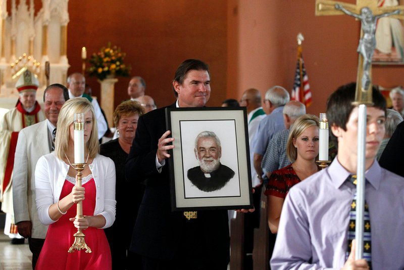 Michael Ginart carries a portrait of his uncle, the Rev. Arthur Ginart, in a procession after a memorial service in the Resurrection of Our Lord Church in New Orleans on Aug. 21. The priest is presumed to have drowned after he chose not to evacuate from his church before Katrina struck in 2005.
