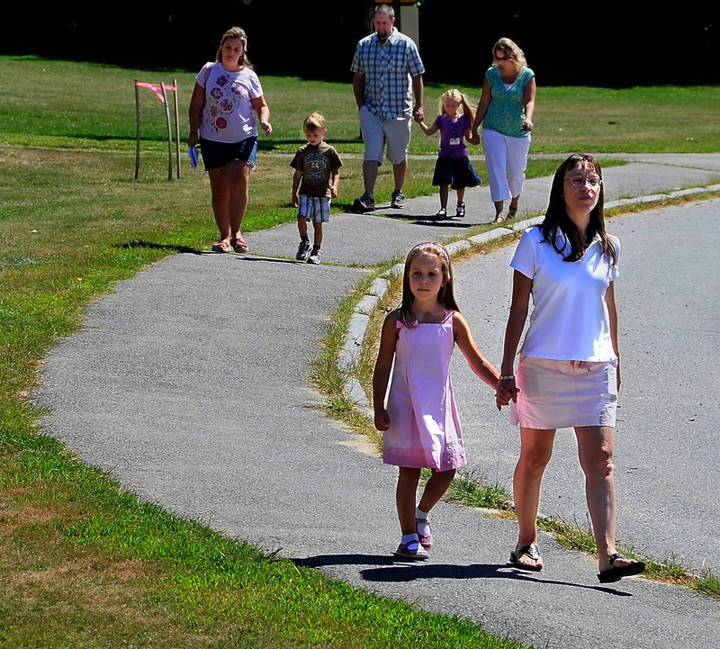 Olivia Bryant, 5, walks to school from the parking lot with her mother, Erica Bryant, as other parents and children follow Monday during the first day of kindergarten and orientation at the Narragansett School in Gorham.