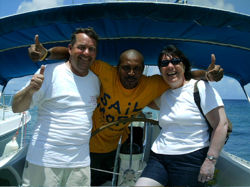 Tim Reardon, the author's husband, and Miriam Gough pose with Seymour, the skipper at the Barefoot Charters sailing school.