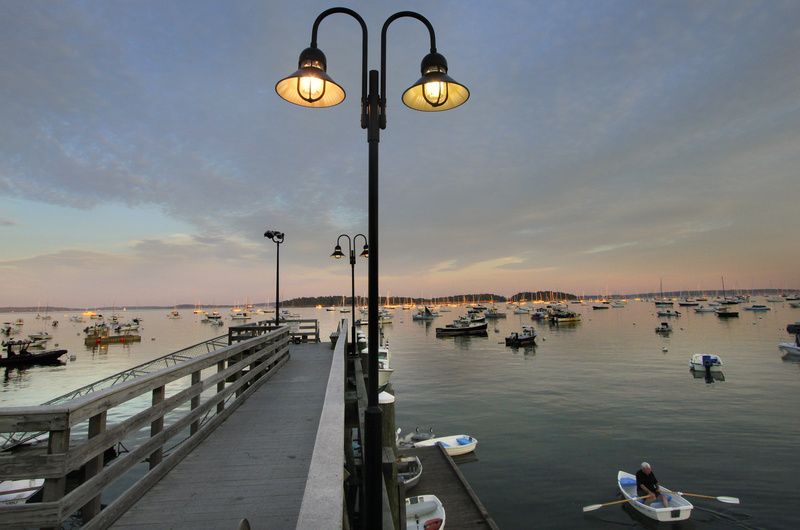 A boater rows past Falmouth Town Landing as the sun begins to fade Tuesday after a pleasant late-summer day. Conditions are expected to be less desirable today, with more clouds than sun, a chance of showers or thunderstorms, and humidity accompanying highs around 78.