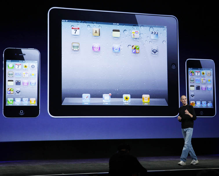 Apple CEO Steve Jobs strolls past a display of the iPhone, left, iPad, and the iPod Touch, right, at news conference in San Francisco today.