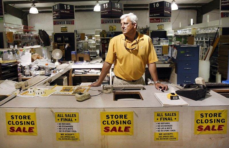 """Surrounded by """"for sale"""" signs, co-owner Bryan Neal contemplates what he might do with the building and property after Depot Building Supply in Lexington, S.C., shuts down this month. The store is closing after three decades, with Neal and his father, Tom, selling off the last of their inventory."""