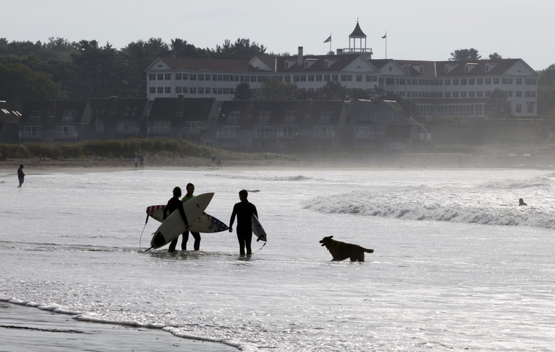 Surfers prepare to head out to take advantage of the waves churned up by Tropical Storm Earl today off of Gooch's Beach in Kennebunk