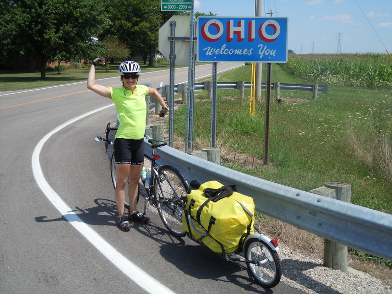 Leah Trommer of Northport celebrates reaching a new state on her cross-country bicycle trip