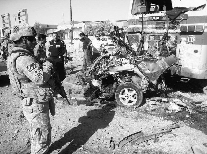 U.S. troops and Iraqi police inspect a bomb-damaged police vehicle in this Aug. 25 file photo after a series of terrorist attacks on Iraqi forces.