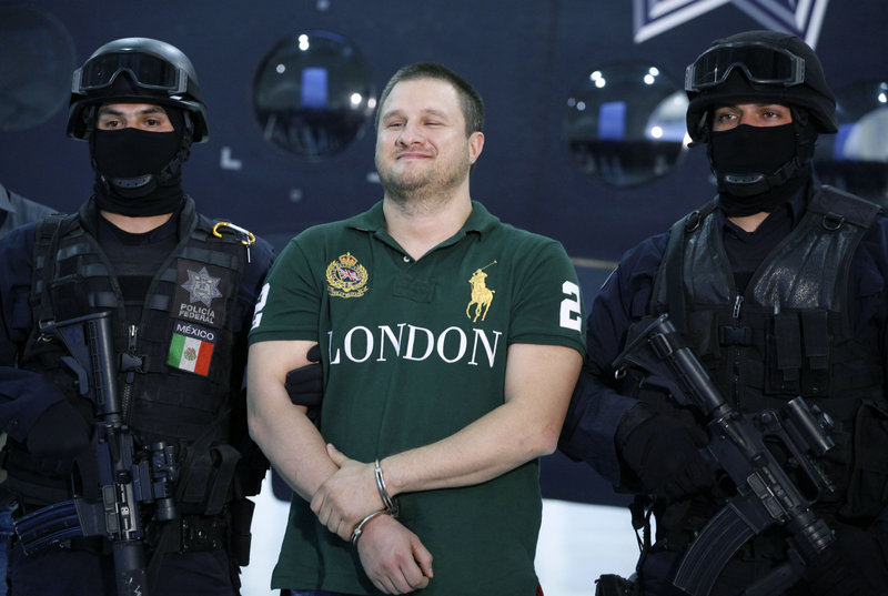 """Mexican police escort Texas-born Edgar Valdez-Villarreal, alias """"La Barbie,"""" in Mexico City on Tuesday. Valdez, the third major suspected drug lord to fall in Mexico in the past nine months, is wanted in the U.S. for allegedly smuggling tons of cocaine and is blamed for a brutal turf war in Mexico."""