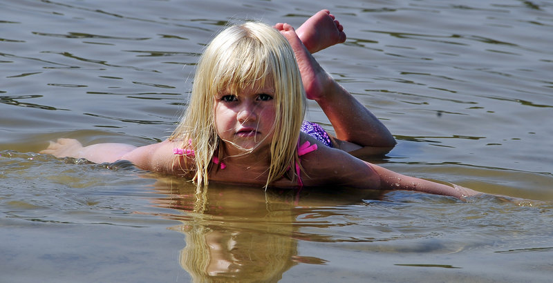 Dylan Gerrish, 4, of Naples makes waves of her own in the shallow water on Sebago Pines Association Beach in Naples on Tuesday.