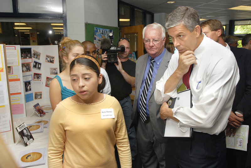 Keyly Martinez, a King Middle School eighth grader, explains her study project to U.S. Secretary of Education Arne Duncan, right, and Principal Mike McCarthy, center.