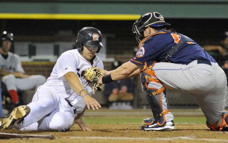 Luis Exposito of the Portland Sea Dogs is tagged out by catcher Luke Montz of the Binghamton Mets during their game Tuesday night at Hadlock Field. The Sea Dogs used strong pitching by Stephen Fife and Ryne Lawson, as well as three home runs, to come away with a 6-0 victory.