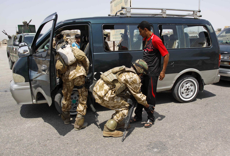 An Iraqi policeman searches a bus as another searches a man at a check point in Basra, Iraq on Wednesday. The U.S. has shifted the focus of the remaining 50,000 American troops from combat operations to preparing Iraqi security forces to protect the country on their own.