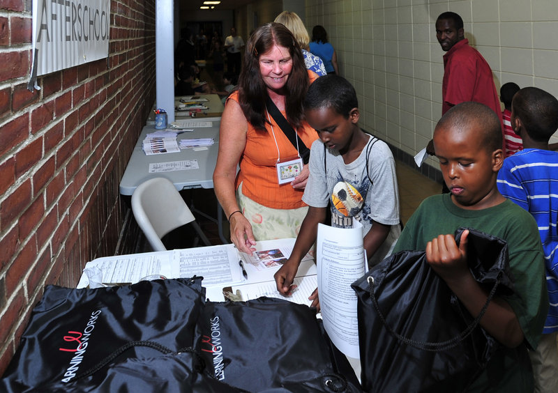 Abdirahim Ali, 9, checks out his new backpack as his friend, Ayub Hiis, 8, signs up Wednesday for his gift, assisted by educational technician Carol Gallagher.