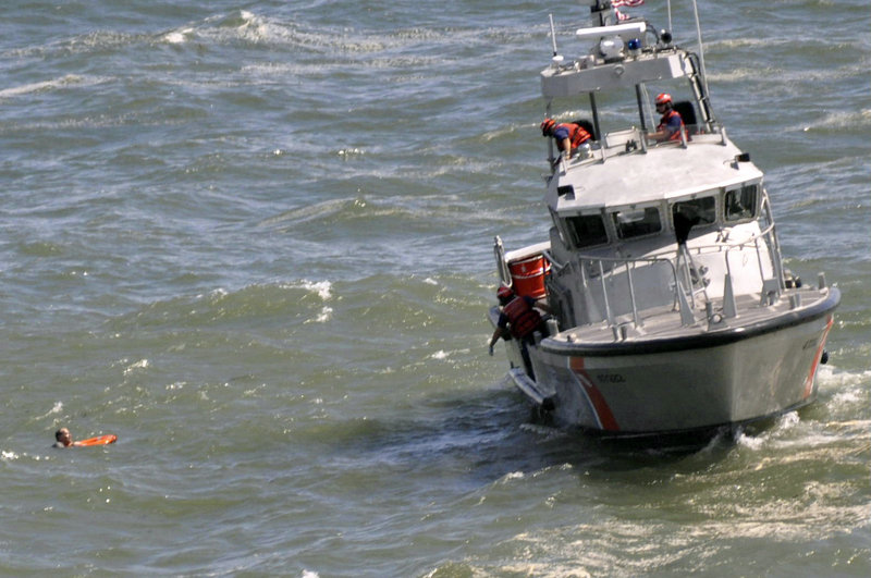 Rescue workers aboard a U.S. Coast Guard boat toss a line to man who'd been swept into the ocean off Acadia National Park last year by waves caused by Hurricane Bill.
