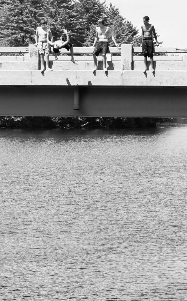 Boys watch as one of their buddies jumps off the bridge that carries Routes 202, 4 and 117 over the Saco River in Buxton last month. Many swimmers still leap from the structure despite warning signs and police efforts to keep them away from the heavily traveled bridge.