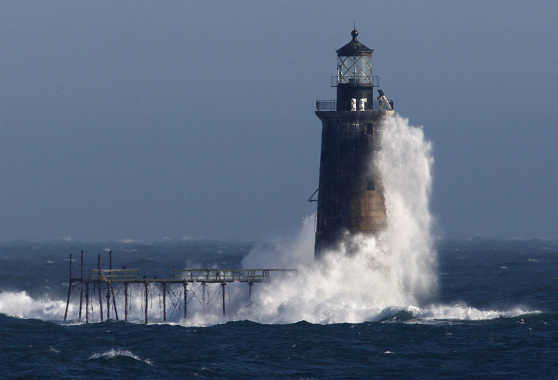 Heavy surf slams into the 72-foot-tall Ram Island Ledge Light at the mouth of Portland Harbor in December 2009. The 105-year-old lighthouse is being auctioned by the federal government.
