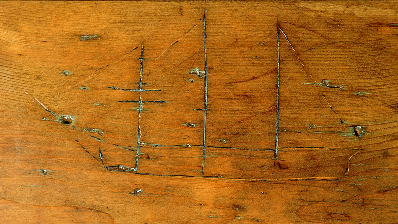 A ship was scratched into a wood panel by a previous owner.