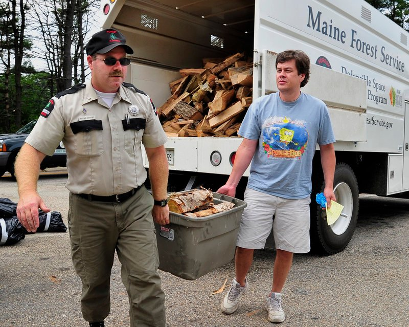 Maine Forest Service Ranger Ritchie Hafford helps John Demoy of Canton, Mass., carry his fresh supply of Maine firewood to his car Friday after exchanging the out-of-state firewood Demoy brought from Massachusetts.