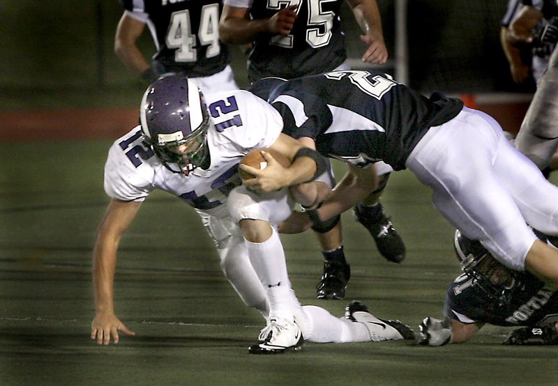 Deering quarterback Jamie Ross pushes forward for extra yardage Friday night while being tackled by Caleb Kenney of Portland in their Western Class A opener at Fitzpatrick Stadium. Ross scored a touchdown with 14 seconds remaining to give the Rams a 21-14 victory.