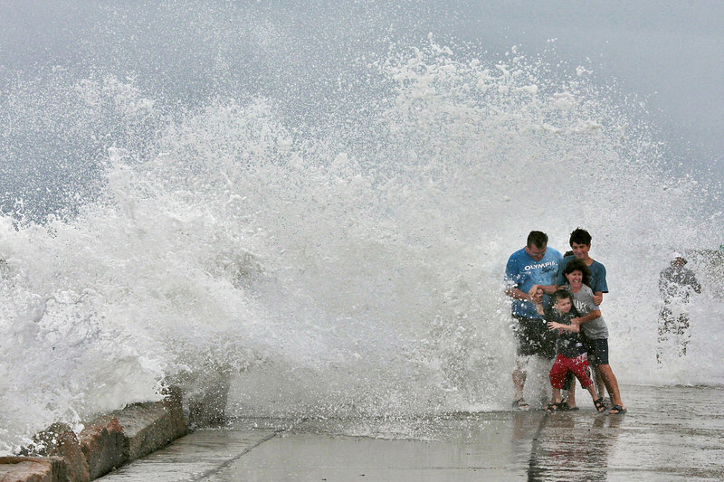 The Gallishaw family from Seekonk, Mass., braces for a large wave crashing over the Goosebury Island causeway in Westport, Mass., on Friday. People were warned to stay off beaches because of the danger of getting swept away.