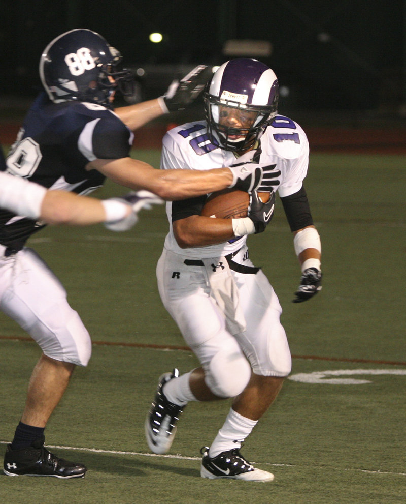 Mike Herrick, who scored a spectacular late tying touchdown on a pass for Portland, prepares to tackle Renaldo Lowry of Deering.