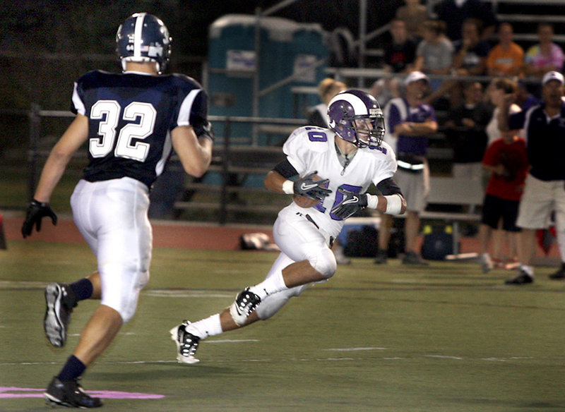 Renaldo Lowry of Deering looks for room while returning a punt Friday night as Carl Szanton of Portland closes in at Fitzpatrick Stadium. Deering, which lost its final six games last season, came from behind for a 21-14 victory.
