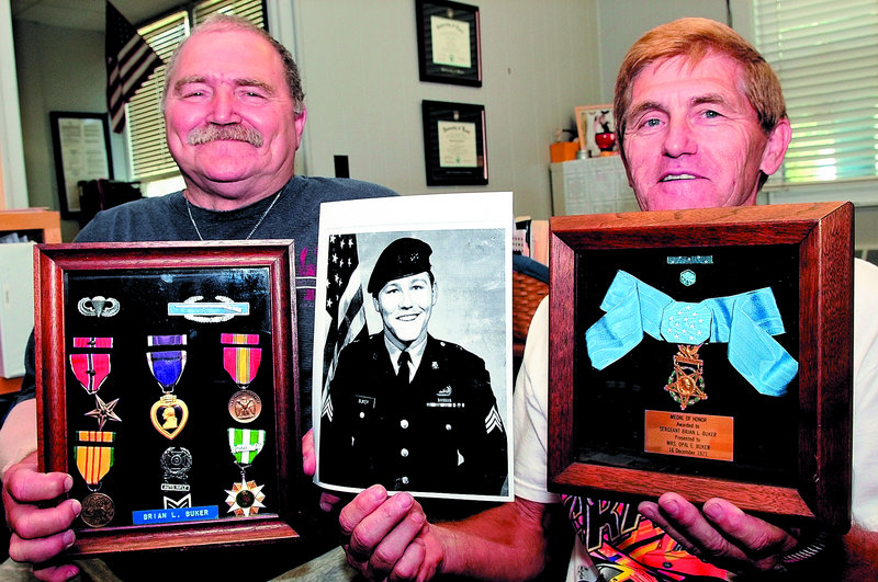 Victor Buker, left, and his brother Alan hold the Medal of Honor and other awards earned by their brother Brian Buker, shown in the photograph, who was killed in Vietnam while serving as a Green Beret in 1967. The Bukers are donating the war memorabilia to Lawrence High School in Fairfield.