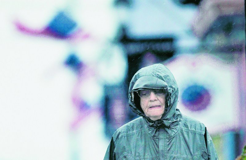 Cathy Black of Dayton, N.J., walks in the rain on the final day of her two-week stay in Lubec as Tropical Storm Earl blows through on Saturday.