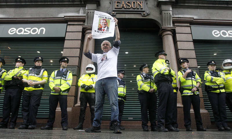 """A protester demonstrates Saturday outside Eason's bookstore in Dublin, where Tony Blair held the first public signing of his memoir, as Irish police look on. Hundreds lined up to get his autograph; opponents of his foreign policies chanted that he had """"blood on his hands."""""""