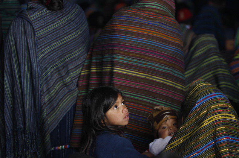 Guatemalan children attend a funeral Mass in Santa Maria Ixtahuacan on Sunday. A tropical depression saturated the ground and set off more than a dozen mudslides.