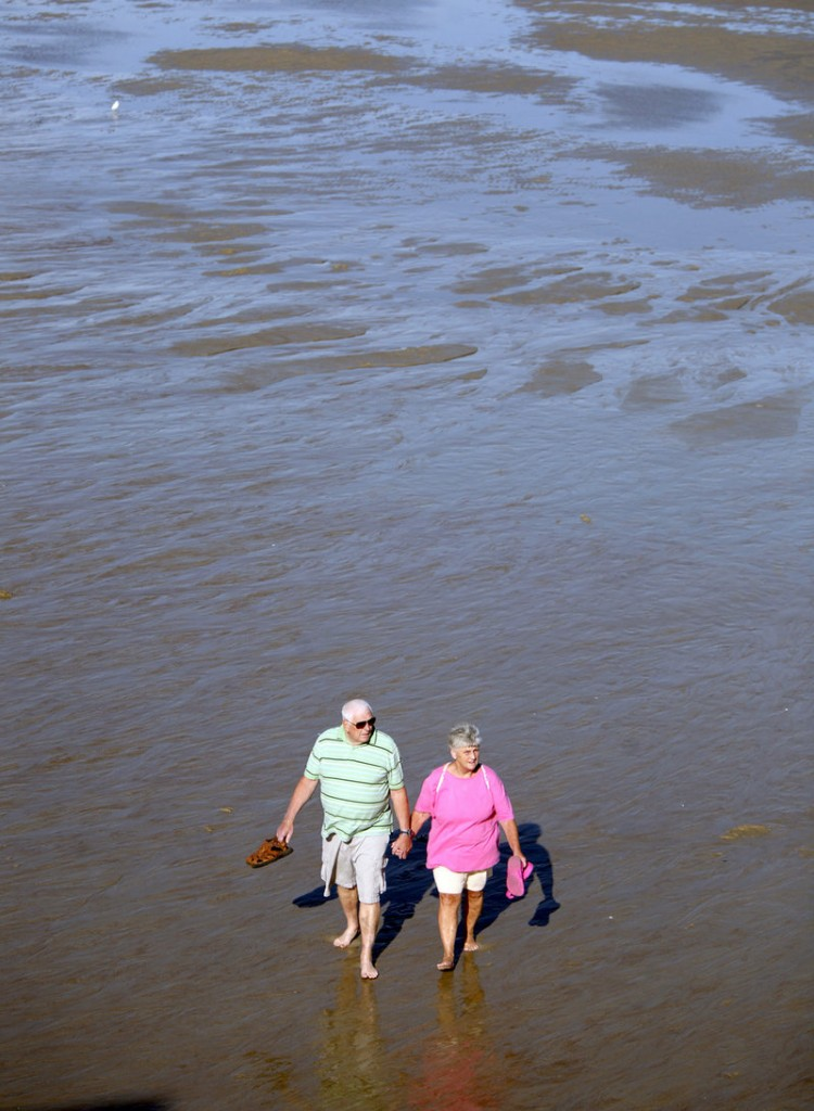 Joe and Joyce Breau of South Portland walk Old Orchard Beach at low tide Monday. They were there to enjoy pier fries and to watch tourists before they left for the season.