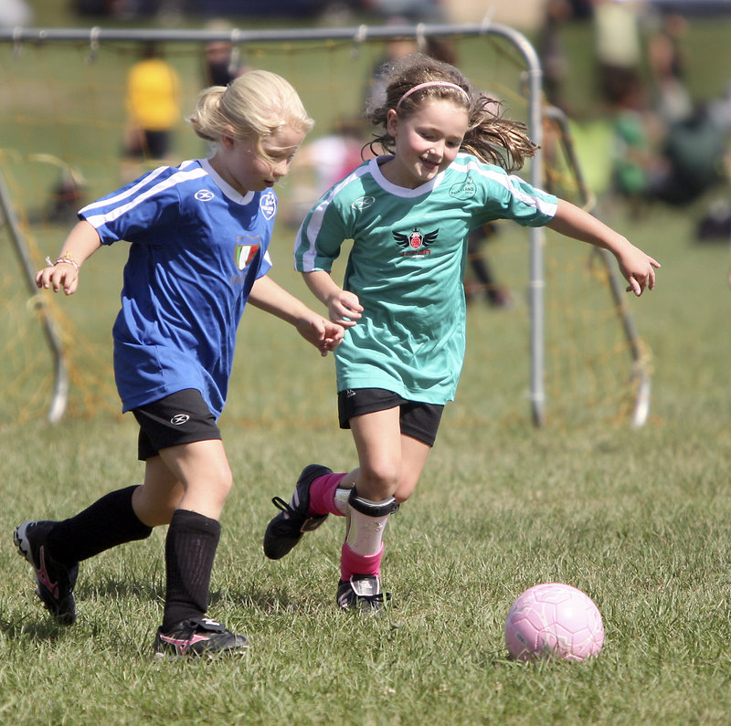 Katie Lederer of Italy, left, defends against Georgia Listell of Japan during their U8 match. U8s play 5 vs. 5 without keepers to reward end-to-end action.