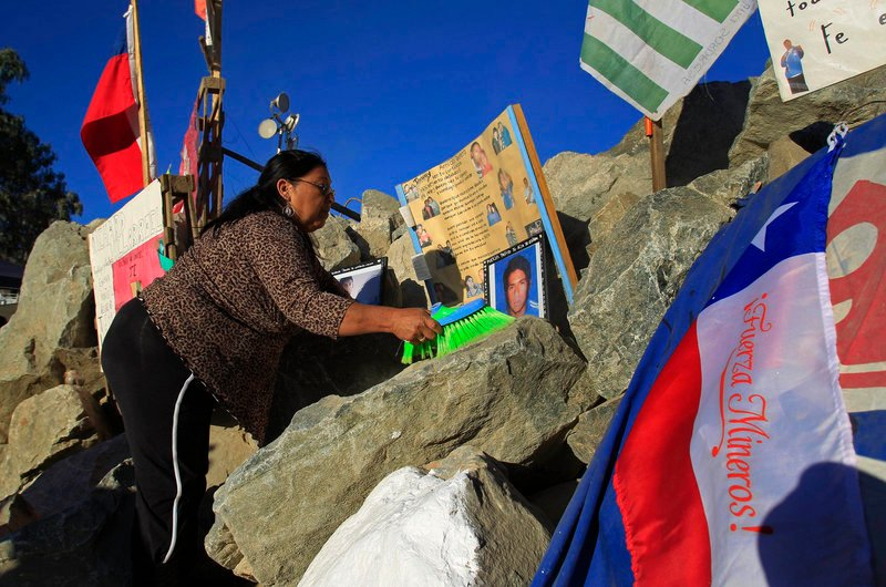 Maria Gomez, an aunt of trapped miner Jimmy Sanchez, cleans his photos on display Tuesday outside the mine where 33 are trapped in Copiapo, Chile.
