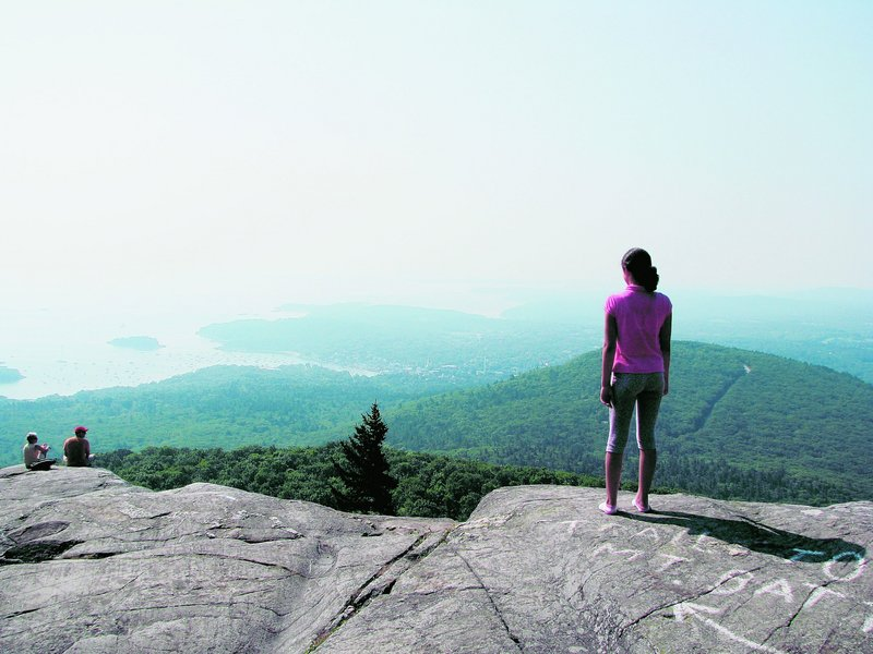 A 12-year-old hiker is rewarded with the view of bay and mountains from Ocean Lookout, at 1,300 feet, on Mount Megunticook.