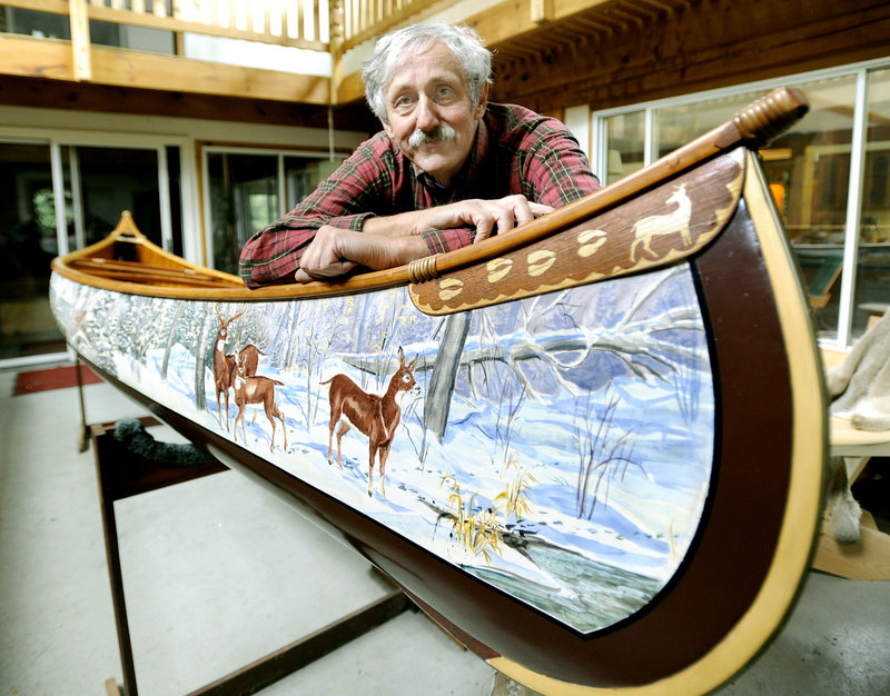 Jerry Stelmok, the owner of Island Falls Canoe in Atkinson, leans on a Millennium Sojourner he painted by hand. When Old Town Canoe and Kayak closed its plant in Old Town a year ago and moved to a smaller facility, it selected Stelmok's company to produce its wooden canoes because of his attention to detail.