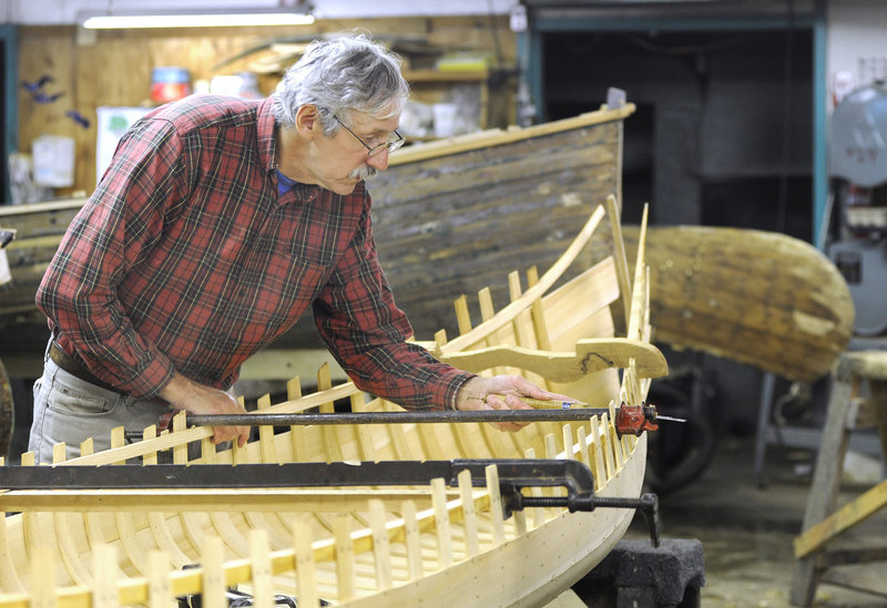 Stelmok works on one of the classic wooden canoes turned out in his factory in Atkinson.
