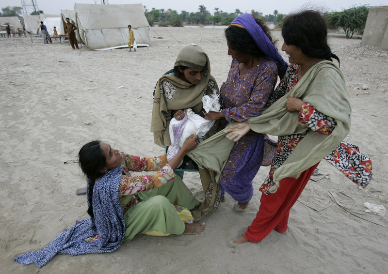 Pakistani women struggle for possession of a package of relief goods thrown from a truck near a camp for people displaced by floods in Punjab province on Wednesday. People in the camp have very few personal belongings and are relying on aid donations.