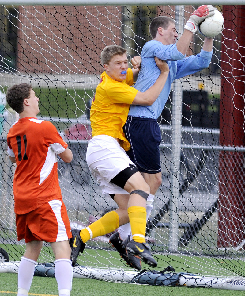 Tim Takach of Cape Elizabeth collides with goalkeeper Jesse Holland of North Yarmouth Academy, who makes the save Wednesday during the Capers' 1-0 victory on a goal in the final minute.
