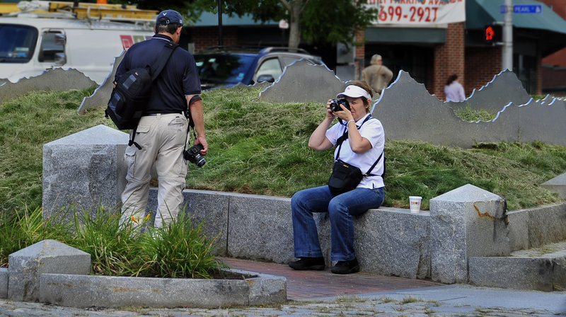 """Gilles Tourigny, a visitor from Montreal, examines """"Tracing the Fore"""" as his wife, Louise Tourigny, takes photos in Boothby Square. Several passing tourists said they liked the piece, but not all understood what it was supposed to be."""