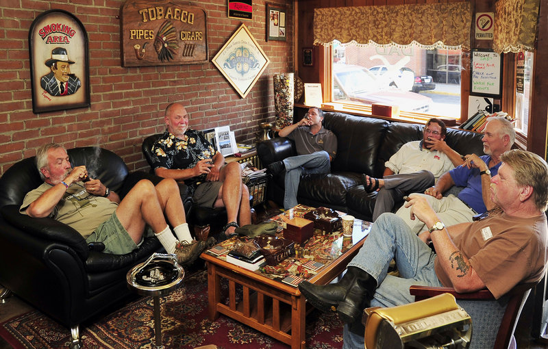 Dan Ducharme, owner of Dad's Cigar Parlor and Tobacco Shoppe in Biddeford, is surrounded by customers enjoying the indoor smoking room with pipe and cigars. Left to right are Daniel Ahern, lighting a pipe, while Dave Colclough, DuCharme, Dale Berube, John Brady and Paul Brake partake of premium cigars in the smoking parlor section of the business. The display cases are in the rear of the store.