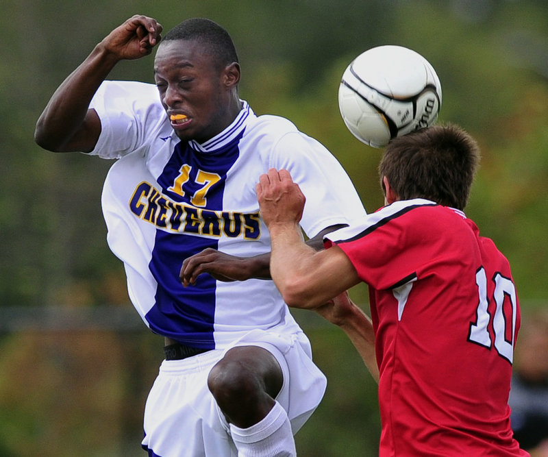 Andrew Guillemette of Sanford, right, heads the ball away from Raphael Tshamala of Cheverus in the first half of their schoolboy soccer game Thursday. Cheverus scored twice in the first half and once in the second to win, 3-0.
