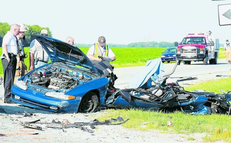 Indiana firefighters, sheriff's deputies and deputy coroners examine the wreckage of a car involved in a fatal crash in 2008. Nationwide traffic deaths in 2009 fell to their lowest level since 1950.