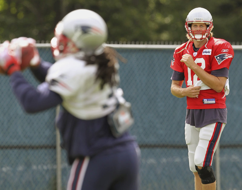 Tom Brady tosses a pass caught by running back Laurence Maroney during the Patriots' practice Thursday. Brady was unhurt in a car accident earlier in the day.
