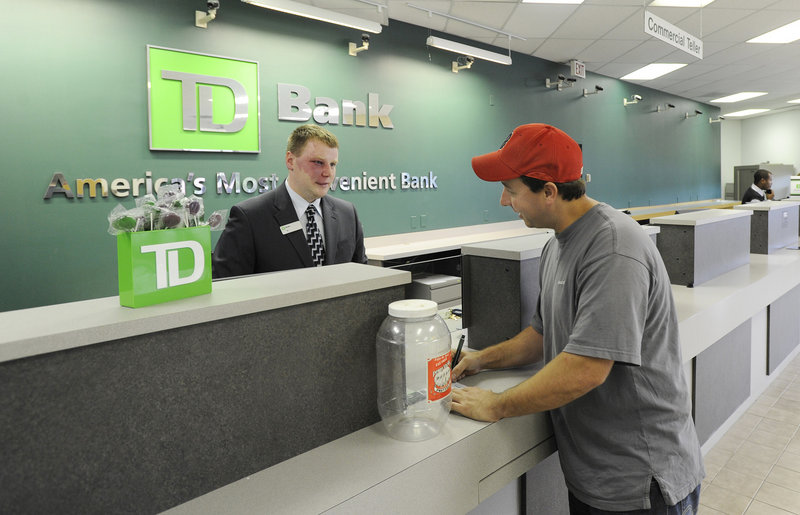 DJ Peterson, a customer service representative, helps Matthew Hodgins open a new account at TD Bank on Allen Avenue in Portland. The bank is open 7 days a week with expanded hours as it focuses on service.